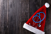 Santa Claus Hat And Doctor Stethoscope On Wooden Rustic Background