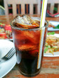 Pop water or cola in glass with ice cubes with food in the background.