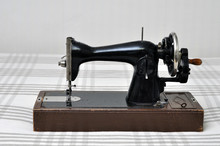 Vintage Sewing Machine With Manual Drive On The Background Of A Linen Tablecloth.