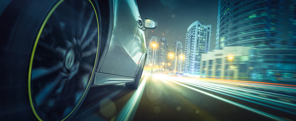 Sportwagen fährt bei Nacht in beleuchteteter Stadt