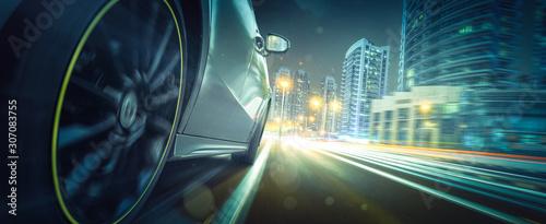 Fotomural Sportwagen fährt bei Nacht in beleuchteteter Stadt