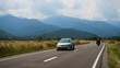 cars on a road leading to mountains at the distance at sunny summer day