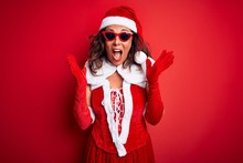 Middle Age Woman Wearing Santa Claus Costume And Sunglasses Over Isolated Red Background Celebrating Crazy And Amazed For Success With Arms Raised And Open Eyes Screaming Excited. Winner Concept