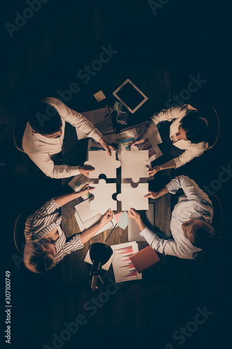High angle above view vertical photo of four business people colleagues sitting table circle working late night holding paper puzzle pieces find unity formalwear indoors