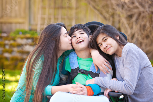 Photo Sisters laughing and hugging disabled little brother in wheelchair outdoors