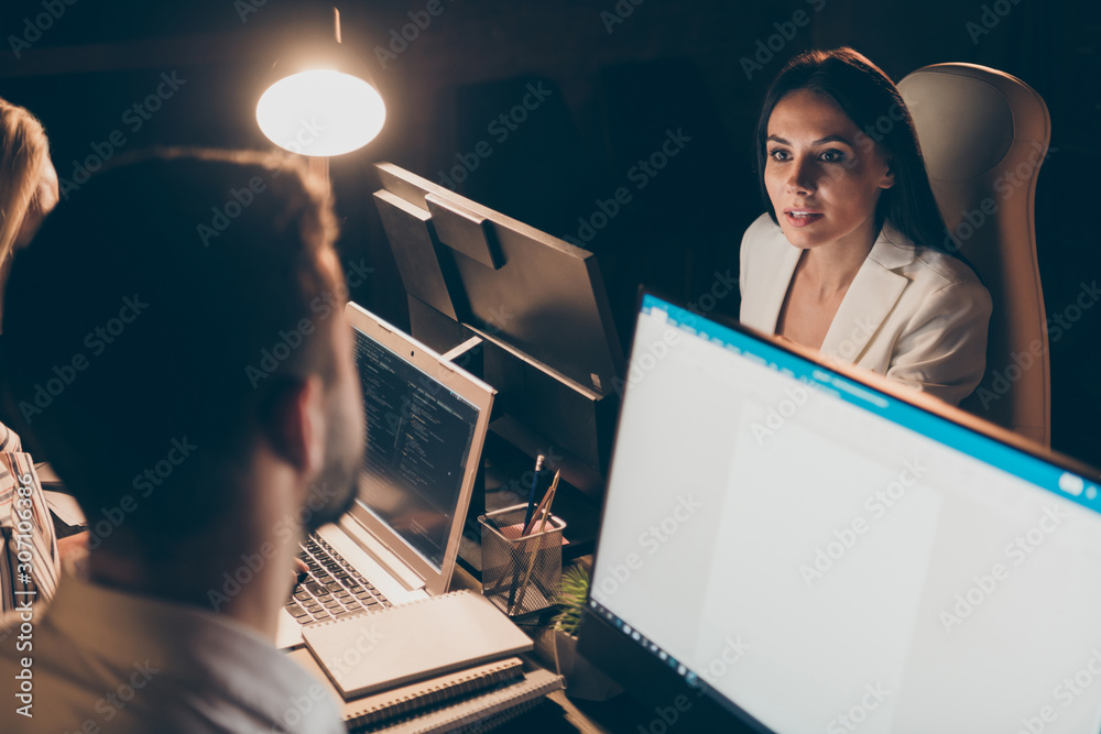 Fototapeta Nice attractive skilled experienced hardworking smart clever coworkers sharks marketers working at night preparing finance report presentation at workplace station indoors