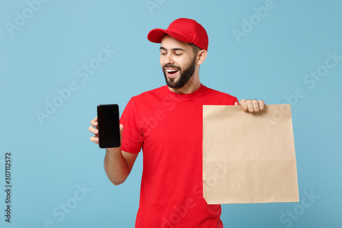 Delivery man in red uniform hold craft paper packet with food isolated on blue background, studio portrait Canvas Print