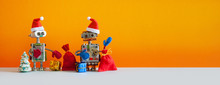 Toy Robots Santas With A Bunch Of New Year's Holiday Gifts And A Christmas Tree. Kind Children's Xmas Greeting Card Mockup. Orange Background Copy Space