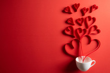 Red Paper Hearts Splash Out From White Coffee Cup On Red Paper Background. Love And Valentine's Day Concept.