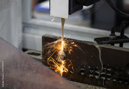 Cuadros en Lienzo Electrical discharge machine EDM cutting workpiece with flying sparks in workshop