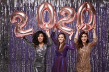 Women In Fancy Sparkling Dresses Posing Isolated Over Vibrant Purple Violet Silver Background. Positive People Spending Time On Happy New Year Holiday Party Discotheque, Hold Inflatable Figures 2020.