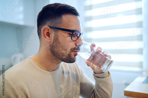 Fototapeta Side view of beautiful caucasian man sitting at dining table and drinking water