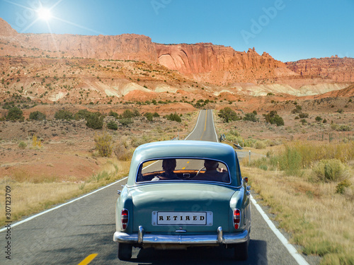 Fototapeta Oldtimer with old couple driving in retirement obraz