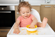 Cute Baby In High Chair Eating Pasta With Hands
