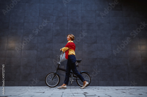 fototapeta na szkło Full length of gorgeous healthy blonde caucasian senior woman pushing bicycle and passing by gray wall.