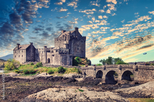 Medieval Eilean Donan Castle in Scotland.  Old fairytale castle near lake in beautiful golden evening light. Medieval castle landscape with sunset in background.