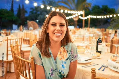 Young beautiful and elegant woman with wedding guest dress smiling happy and cheerful at party feast