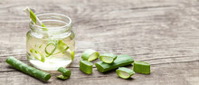 Aloe Vera Green Cocktail For Healthy Body And Body. Aloe Pulp Slices In A Glass Jar And Leaves On A Wooden Table