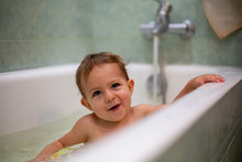 Cute Caucasian Baby Taking A Bath, Smile Playfully And Look Up, Resting On The Side Of The Bath. Water Splashes, In The Background A Green Bathroom In Blur. Close-up, Soft Focus