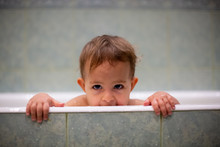Cute Caucasian Baby Peeks Out Of The Bathtub, Put Hands On The Side Of The Bath And Looks To The Camera Playly. In The Background Is A Green Bathroom In Blur. Close-up, Soft Focus