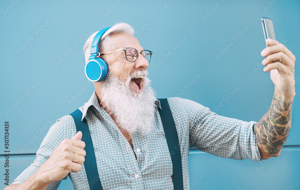 Fototapeta Happy senior man taking selfie while listening music with headphones - Hipster mature male having fun using mobile smartphone playlist apps - technology and elderly lifestyle people concept