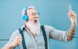 Happy senior man taking selfie while listening music with headphones - Hipster mature male having fun using mobile smartphone playlist apps - technology and elderly lifestyle people concept