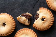 Broken Open Traditional British Christmas Mince Pie With Fruit Filling Next To Whole Mince Pies On Black Slate. Top View. Copy Space.