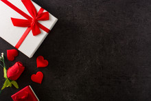 Gift Box And Red Paper Envelope Decorated With Red Heart On Black Background. Copy Space