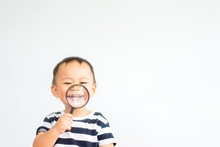 Little Toddler Boy Child Holding Magnifying Glass And Showing Front Teeth With Big Smile On Green Grass: Healthy Happy Funny Smiling Face Young Adorable Lovely Boy Kid With New Tooth Dental.