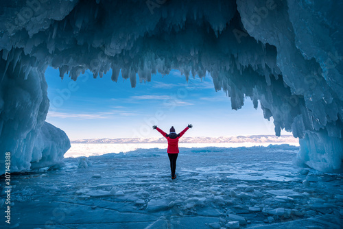 Traveler woman wear red clothes and raising arm standing on frozen water in ice cave at Lake Baikal, Siberia, Russia Canvas Print