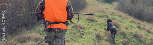 Valokuva A man with a gun in his hands and an orange vest on a pheasant hunt in a wooded area in cloudy weather