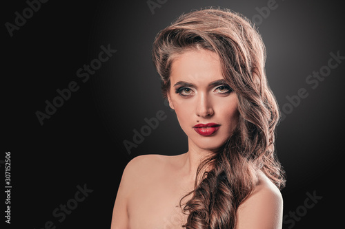 glamorous young woman with evening makeup touching her face.
