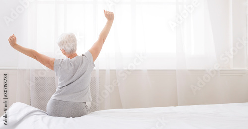 Well slept senior woman stretching with arms raised on bed Canvas Print