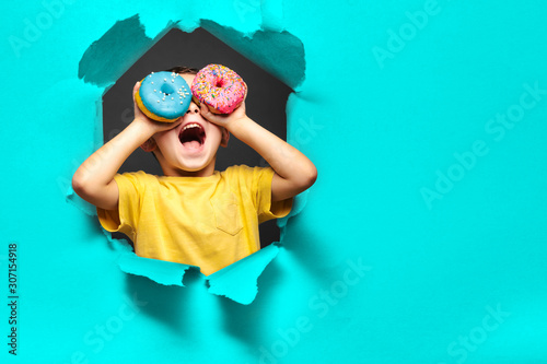 Happy cute boy is having fun played with donuts on black background wall Wallpaper Mural