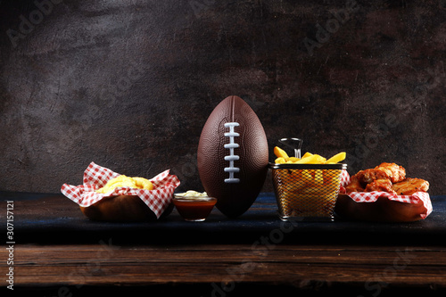 Fototapeta chicken wings, fries and onion rings for football on a table. Great for Bowl Game party obraz
