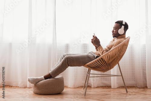 Fototapeta Millennial Afro Guy In Headphones Using Smartphone Sitting Indoor obraz na płótnie