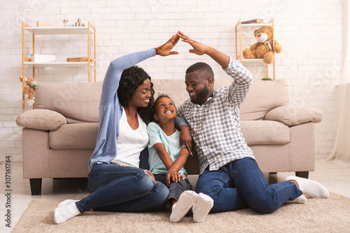 Canvastavla Black parents making symbolic roof of hands above little daughter's head