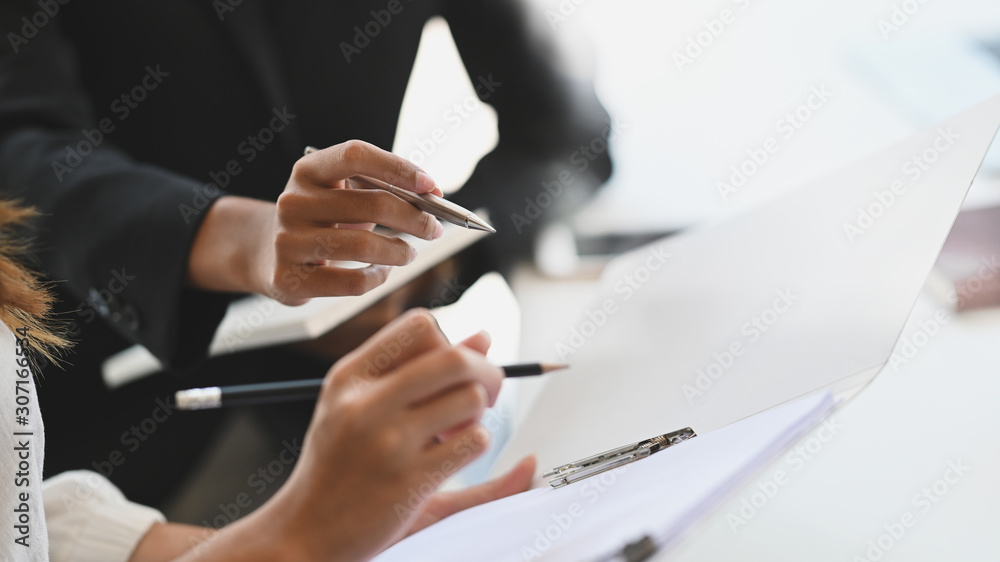 Fototapeta Closeup two woman consulting with paperwork document report.