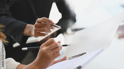 Fototapeta Closeup two woman consulting with paperwork document report. obraz
