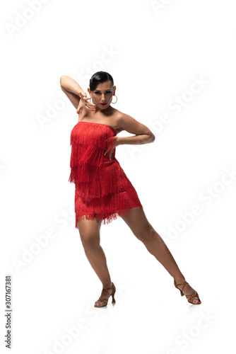 attractive, passionate dancer in red dress with fringe looking at camera while performing tango on white background