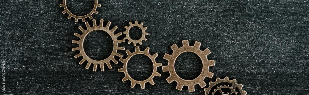 Fototapeta top view of retro metal gears on dark wooden background, panoramic shot