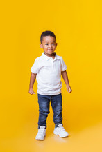 Portrait Of Smiling Little Black Boy In Jeans And White T-shirt