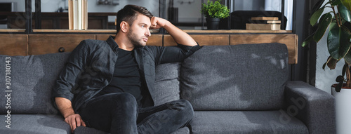 Photo panoramic shot of handsome and pensive man sitting on sofa in apartment