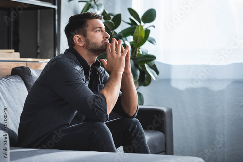 Photo side view of handsome and pensive man sitting on sofa and looking up in apartmen