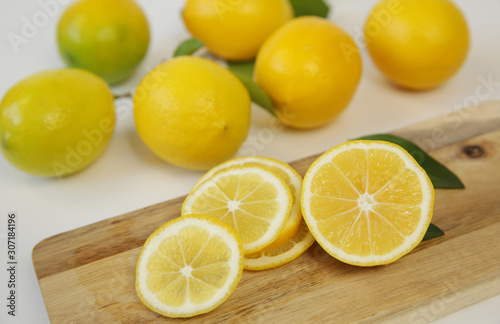 slices of juicy lemons on a cutting wooden board and pile of lemon on a white background. Organic citrus fruits for a healthy diet. Tropical fruit. Close-up.
