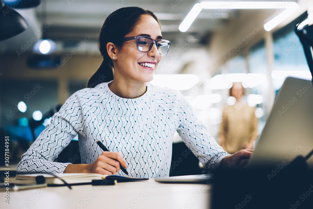 Fototapeta Cheerful businesswoman excited with accomplished project successfully monitoring news online via netbook, smiling female administrative manager happy about increasing company income making report