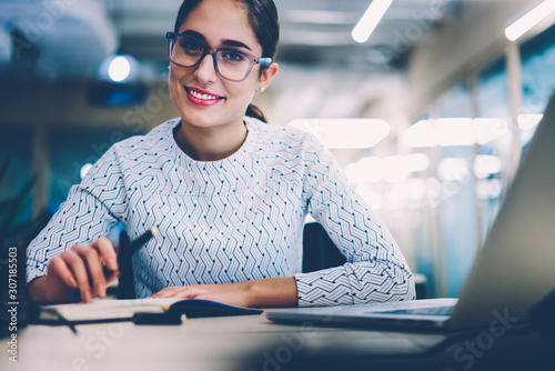 Fototapety, obrazy: Smiling businesswoman in eyewear looking at camera organizing working process sitting at desktop,portrait of successful female manager satisfied with occupation planning project strategy in office