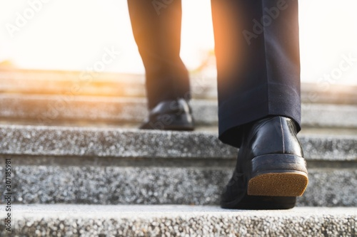 Obraz Image of a man walking up the stairs to achieve the goal - fototapety do salonu