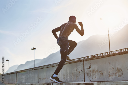 Obraz Athletic man exercising on stadium tribune. - fototapety do salonu