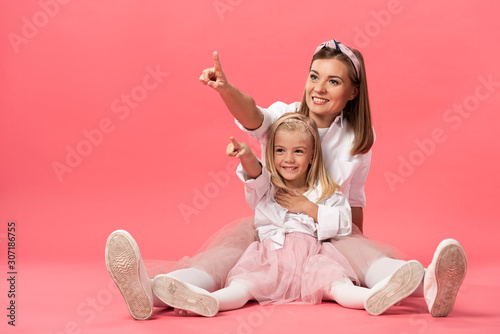 Obraz smiling daughter and mother pointing with fingers on pink background - fototapety do salonu